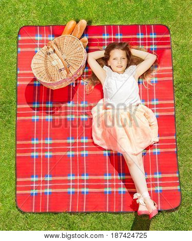 Top view portrait of beautiful blond girl in summer clothes relaxing on the red checkered blanket next to the picnic basket
