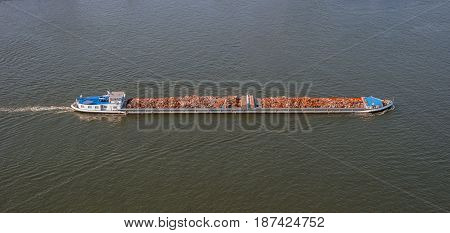 Waste disposal on large heavy cargo ship. Boat with scrap metal. Environment concept vessel shipping garbage in sea. Aerial view of boat carrying waste on river. Barge transports construction debris