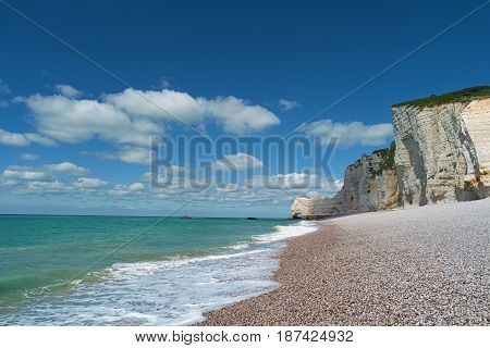 Blue sea pebble beach and cliffs in Etretat France Europe. Popular landmark famous destination of Normandy. Beautiful summer landscape seascape. Scenic view of ocean wave stones on sunny day