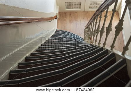 Traditional staircase in old house of Amsterdam Netherlands Europe. Narrow stairs in Holland. Spiral circle staircase in home interior architecture of building. Upside view of high helical stairs