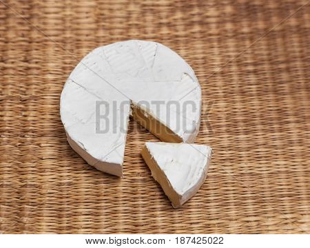 Fresh slice of Camembert cheese natural, on a straw Mat