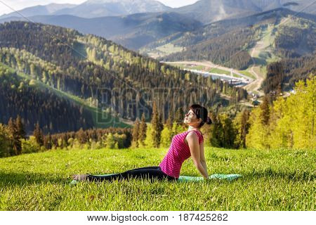 The young woman sitting on a mountaintop. The concept of a healthy lifestyle travel and yoga.