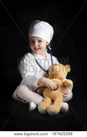 Little girl in a medical suit plays at the doctor