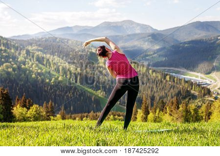 The young girl practices yoga on top of mountains. The concept of a healthy lifestyle travel and yoga.