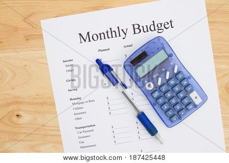 Creating a monthly budget A print out of a monthly budget with pen and calculator on a desk