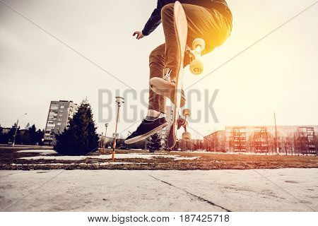Man young skateboarder legs skateboarding at skatepark On Sunset. Concept tricks and jumping on a skateboard