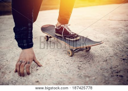 The skateboarder guy is getting ready for the start before the trick on the skateboard. Concept forward to the goal.