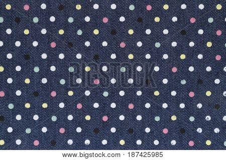 Dark blue denim with multicolored polka dot fabric background