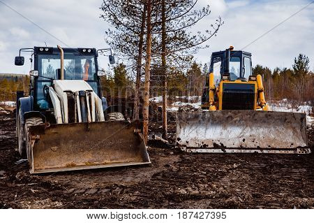 Tractor loader and bulldozer on a caterpillar drive is parked in the mud. Concept road construction.