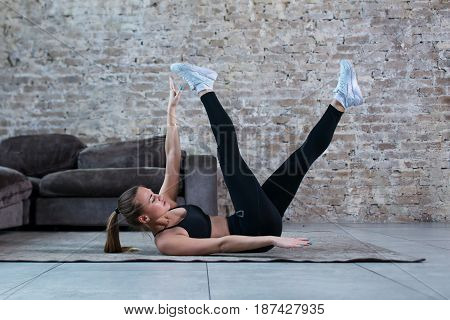 Sportswoman training at home. Fit female athlete doing toe touch single arm exercise lying on floor in loft apartment.
