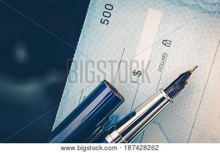 Check Issuing Concept Closeup Photo. Business Check and the Elegant Fountain Pen. Executive Desk.