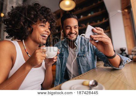 Young man showing something on cellphone to his girlfriend at cafe. Happy young couple sitting at coffee shop having video chat on mobile phone.