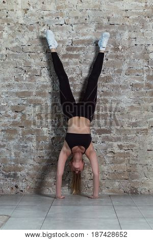 Front view of young fit female athlete doing handstand exercise against brick wall.