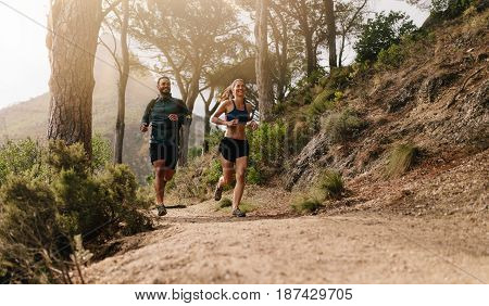 Young Sporty Couple Running In The Mountains