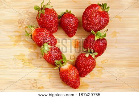 Dark red strawberry which is spread out in the form of heart on a chopping board
