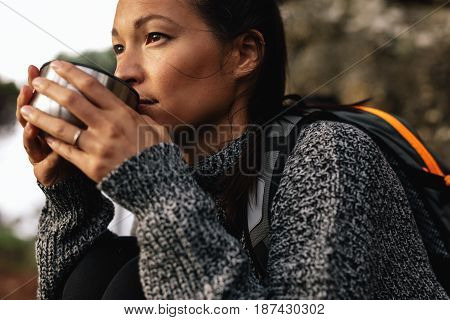 Close up shot of young female hiker drinking coffee. Female hiker taking break during hike.