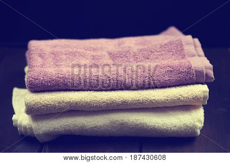 Stacked spa towels over dark brown wooden background