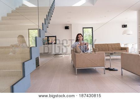 Beautifull young woman in a bathrobe enjoying morning coffee in her luxurious home villa