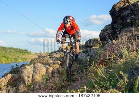 Cyclist in Red Jacket Riding the Mountain Bike on the Beautiful Spring Rocky Trail above the River. Extreme Sport Concept