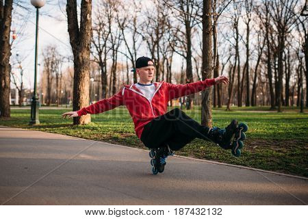 Roller skater doing balance exercise on sidewalk