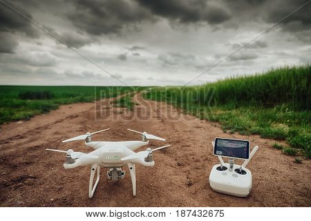 Remote Control And Drone On A Green Field