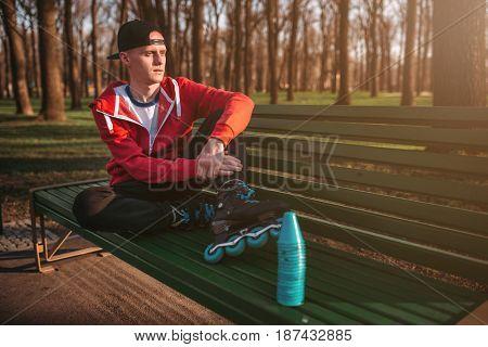 Roller skater posing on the bench in skates