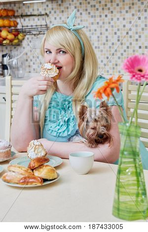 Plump smiling woman holding little dog sits eating homemade baked sweets at table in kitchen.