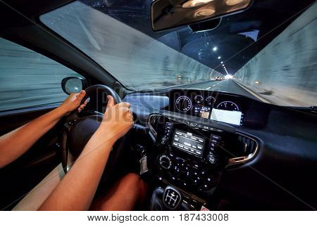 Hands of woman who drives car in illuminated tunnel.