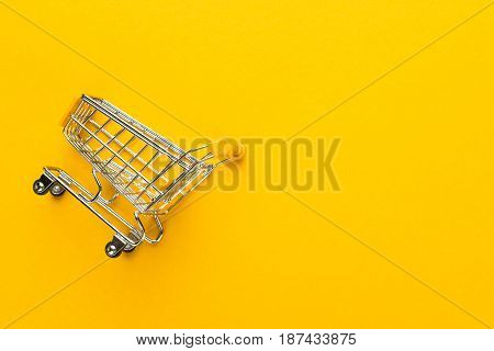 shopping trolley on yellow background. shot of shopping trolley with some copy space. yellow shopping trolley on seamless background. shopping concept with shopping trolley