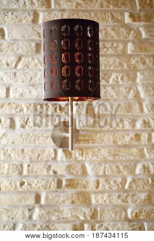 Brown wall bracket lamp are on white brick wall, close up view