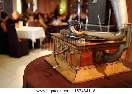Old gramophone and people in restaurant, focus on gramophone, translation of text - gramophone factory RSFSR