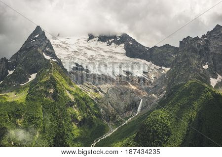 mountains with green grass. snow tops on the mountains. stormy sky over mountains. mountain landscape.