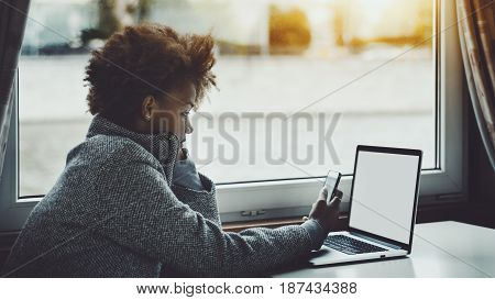 Concentrated young afro american freelancer female with curly black hair using smart phone as wi-fi internet modem for her modern laptop with blank white mock-up screen while sitting in ship cabin