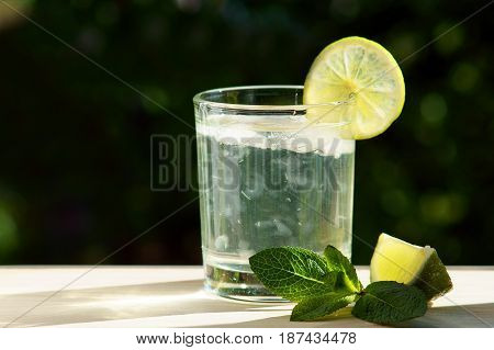 Mojito with lime slice on a green background