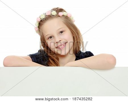 Beautiful little girl with a wreath on his head peeks out from behind the banner.Isolated on white background.