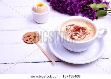Cup of cappuccino with a saucer on a white wooden background behind a bouquet of purple lilacs