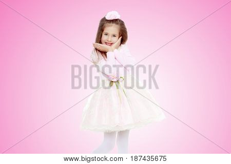 Dressy little girl long blonde hair, beautiful pink dress and a rose in her hair.She holds the palm of your hand near their cheeks.Pale pink gradient background.