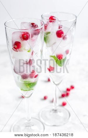 ice cubes with fresh red berries and mint leaves in glasses on white table background