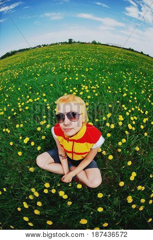 Portrait of beautiful happy cute girl with short blonde hair in yellow with red stripes tank top in sunglasses sitting in the meadow with dandelions. Photo taken with a fisheye effect.
