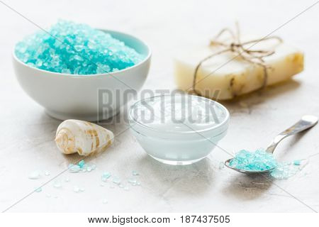 blue homemade spa composition with blue sea salt and natural soap on stone desk background