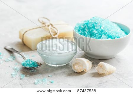 organic set for bath with blue salt and shells on stone table background