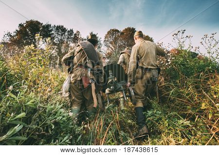 Reenactors Dressed As Russian Soviet Red Army Soldiers Of World War II Walking With With Maxim's Machine Gun Weapon In Autumn Meadow.