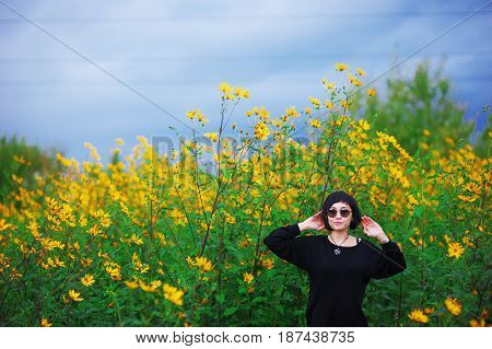 Portrait of young beautiful brunette woman with stylish haircut in a black jumper wearing sunglasses in the field among the yellow flowers of Jerusalem artichoke.