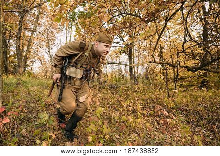 Dyatlovichi, Belarus - October 2, 2016: Reenactor Dressed As Russian Soviet Red Army Soldier Of World War II Hidden Running With Sub-machine Gun PPS-43 In Autumn Forest At Historical Reenactment