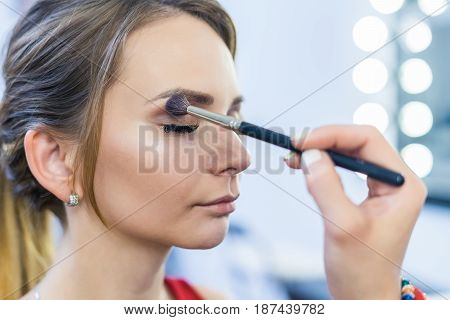 Make-up artist doing smoky eyes makeup to beautiful young girl in the studio Dressing room