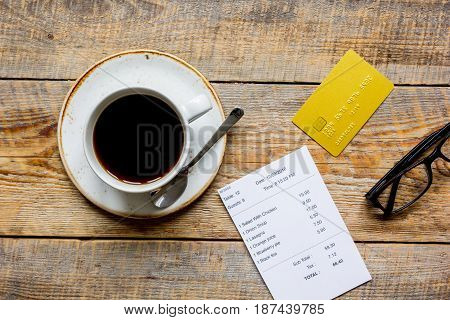 cup of coffee and receipt bill for payment by credit card on wooden table background top view