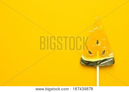 sugar watermelon lollipop on bright yellow background with some copy space