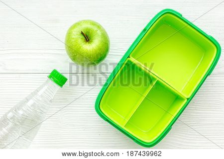 healthy break with apple, bottle and green lunchbox on home wooden table background flat lay mock-up