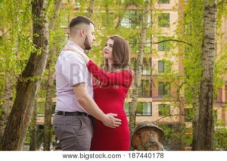 Happy young couple expecting baby in summer park.
