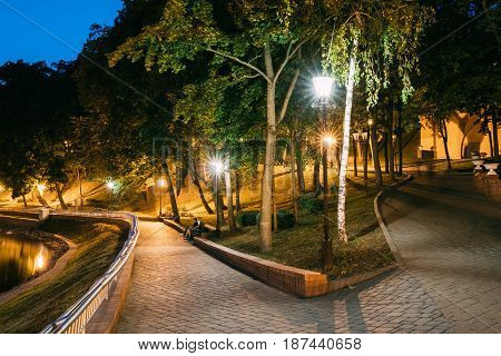 Gomel, Homiel, Belarus. Lighted Walkways Or Roads, Greenwood At Blue Hour Of Evening Or Night In City Park. Popular Place For Tourists And Locals In Gomel, Belarus.